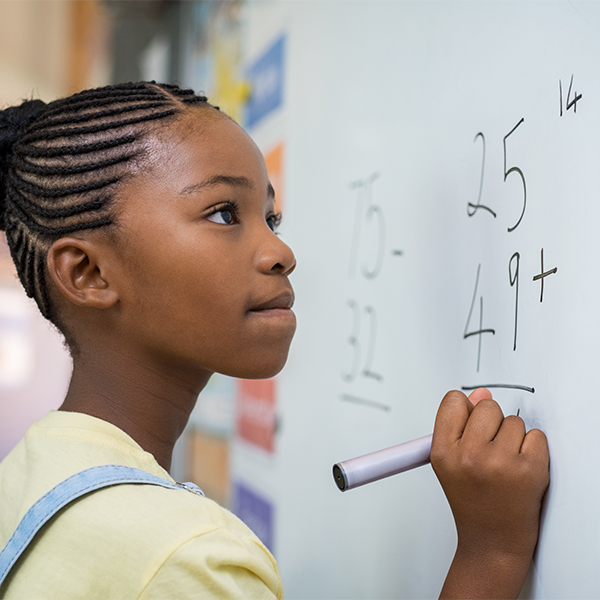 Girl solving a math problem at a white board